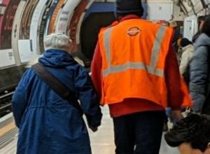 A station worker assists a passenger